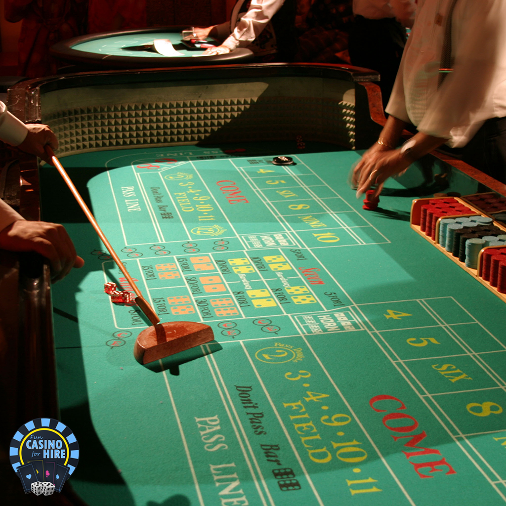 Craps dealer with rake chips and dice
